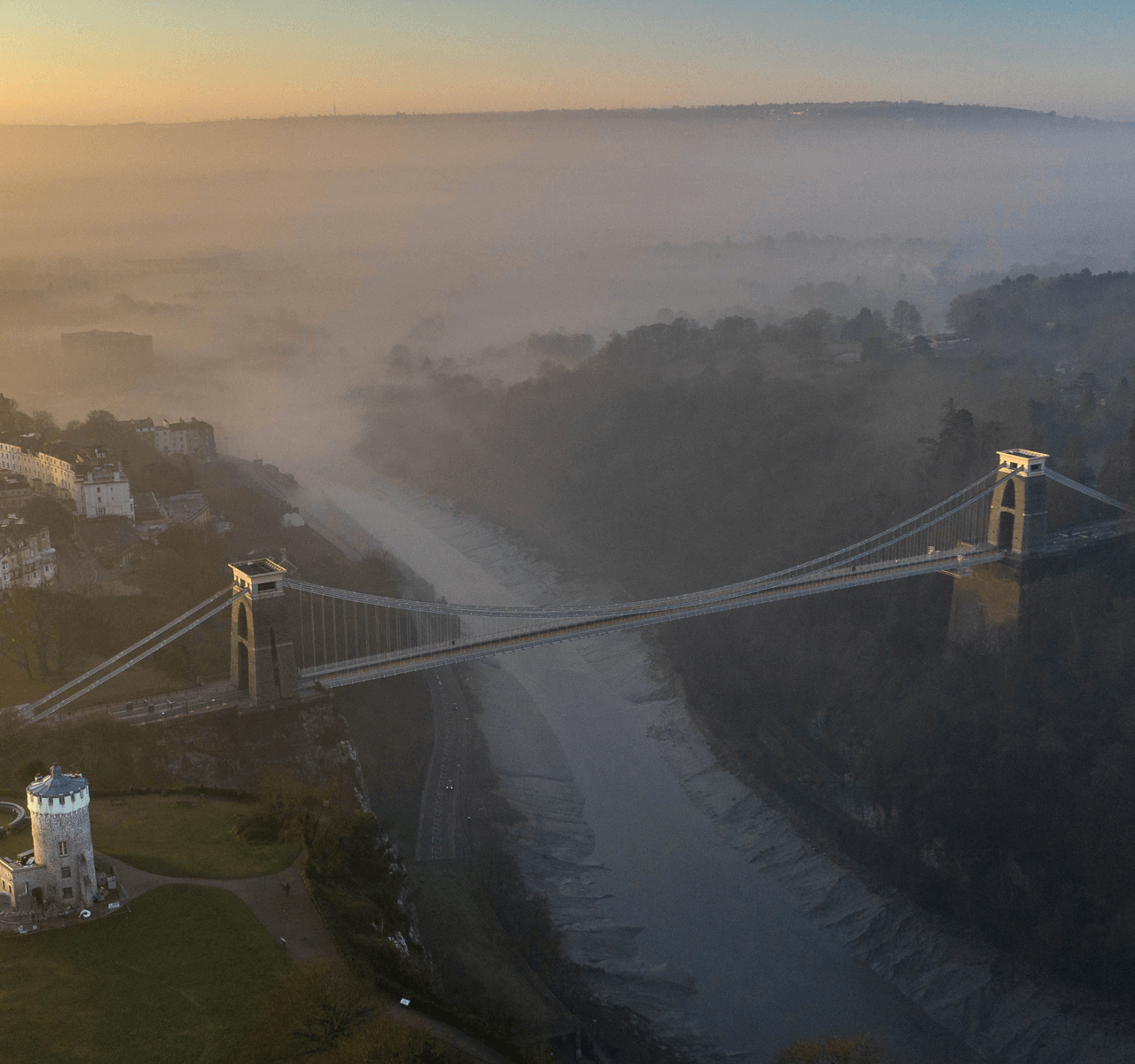 """Mavic 2 Pro"" aerial drone photo of ""Clifton Suspension Bridge"" and the ""Clifton Observatory"" on during a foggy sunrise"