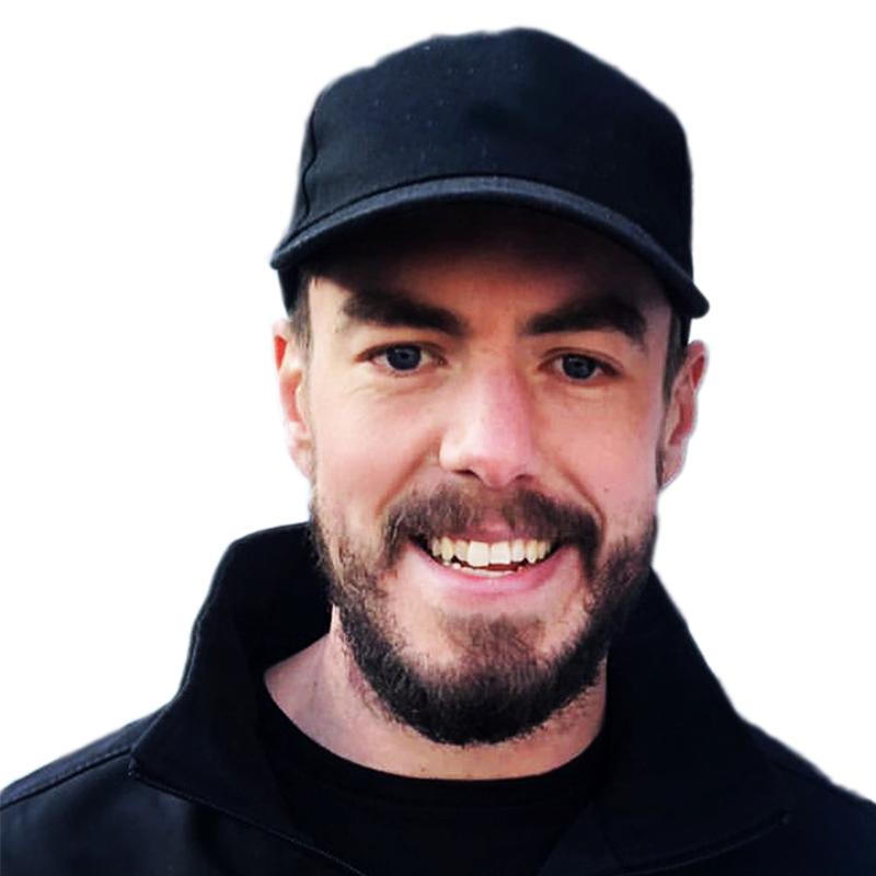 Portrait head shot photo of Tom Osborne wearing a black baseball cap